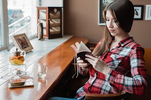 Girl brunette with long beautiful hair in a shirt, in day in cafe by the window, looks at a paper notebook. Next to the smartphone. A teapot with a mug of tea.