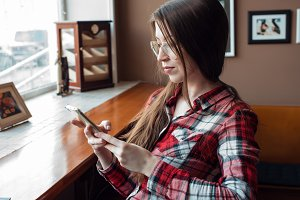 The brunette girl with glasses and a shirt, in the daytime in a cafe by the window, in her hands a smartphone, reads a message, sits in social networks.