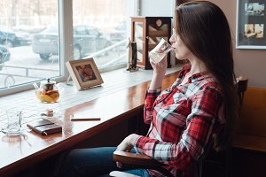 The brunette girl with glasses and a shirt, in the afternoon at a cafe by the window, drinks tea in the morning. Next to the table there is a kettle with a telephone and a paper pad.