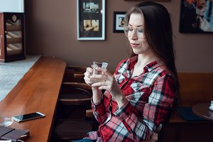 The brunette girl with glasses and a shirt, in the afternoon at a cafe by the window, drinks tea in the morning. Next to the wooden counter there is a telephone and a paper pad.