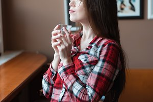 The brunette girl with glasses and a shirt, in the afternoon at a cafe by the window, drinks tea in the morning. Holds a mug enjoying a drink.