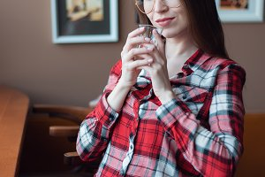 The brunette girl with glasses and a shirt, in the afternoon at a cafe by the window, drinks tea in the morning. Holding a mug happy smiling. Sits in a chair.