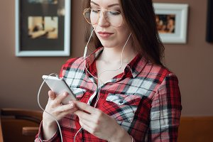 A girl in a shirt, in a cafe by the window, is holding a smartphone, wearing headphones and glasses, listening to music. A woman is sitting in a social network watching a video.
