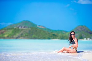 Young beautiful woman having fun on tropical seashore. Happy girl on white sand tropical beach