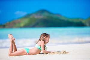 Adorable little girl lying on white sandy beach