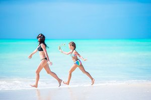 Beautiful mother and daughter on Caribbean beach have a lot of fun together