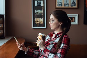 The brunette girl with glasses and a shirt, in the afternoon at a cafe by the window, drinks tea in the morning. He holds a glass in his hand. Sits in a chair. In the hands of the phone, looks at the message, checks social networks.