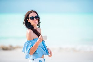 Young beautiful woman on tropical seashore. Happy girl walking at white sand tropical beach