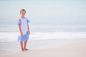 Beautiful little girl in dress at beach having fun. Happy girl enjoy summer vacation background the blue sky and turquoise water in the sea on caribbean island