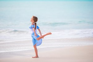 Adorable little girl on the beach. Happy girl enjoy summer vacation background the blue sky and turquoise water in the sea