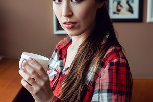The woman in the shirt. The brunette girl with long hair. In the hands of a cup of coffee or tea. Posing with a surprised emotion on his face. Afternoon in a cafe by the window.