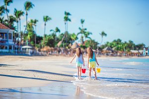 Rear view of little beautiful girls walking on tropical seashore