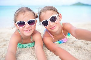 Close up little girls on sandy beach. Happy kids lying on warm white sandy beach