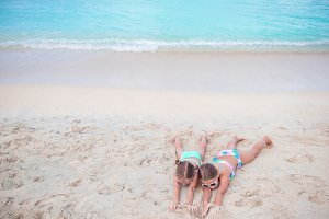 Cute little girls on sandy beach. Happy kids lying on warm white sandy beach