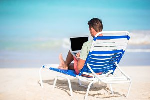 Young man with laptop on tropical beach. Man sitting on the chaise-lounge with computer