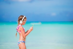 Little girl with headphones on the beach