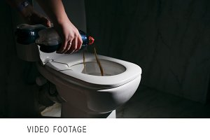 Pouring out cola into the toilet