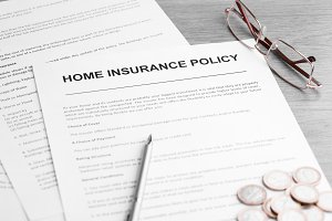 Home Insurance Policy. Pen, Glasses and Coins on a Table