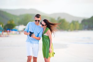 Young couple on beach vacation looking at camera