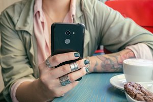 tattooed girl with smartphone