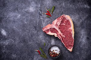 Raw T-bone steak with spices
