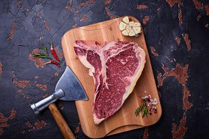 Raw T-bone steak with hatchet