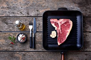 Raw T-bone steak on iron grill pan