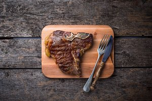 Grilled T-bone steak on wooden board