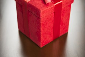 Gift & Red Ribbon on Wood Surface