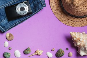 Clothes, Photo Camera, Brown Hat, Seashells on Lilac Background. Top View Travel Concept with Copyspace.