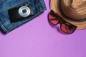 Jeans, Sunglasses, Photo Camera, Brown Hat on Lilac Background. Top View Travel Concept with Copyspace.