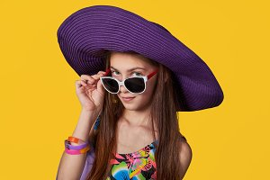Bright closeup fashion studio portrait of pretty young girl teenager. Stunning young woman in elegant hat, colorful swimsuit and sunglasses looks at the camera. Concept fashion, summer, travel.