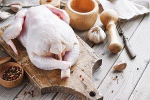 chicken carcass on a wooden background with spices, cooking in the kitchen, rustic style