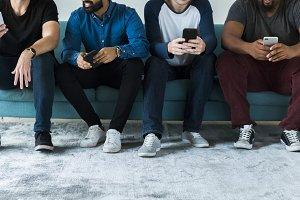 Diverse men using mobile phone
