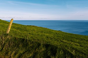 Scenic view of green grass hill and Atlantic Ocean in Ireland co