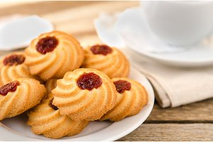 Biscuits with jam on wooden table with a mug of tea