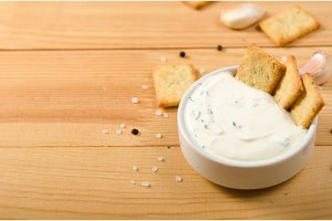 Salted snacks with pepper, salt greens in white sauce. Wooden table