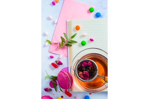 Feminine flat lay with tea, sweets and open book with empty pages. Colorful party background with confetti. Planning concept with copy space.