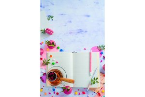 Feminine writer workplace with an open notepad or diary. Colorful sweet snacks, hard candy, and pink macarons on a light wooden background with copy space.
