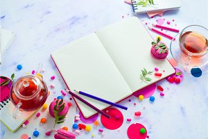 Feminine background with tea, pink sweets, candies, confetti and open book with empty pages. Colorful planning party concept with copy space.
