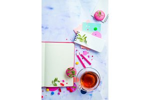 Colorful flat lay with an open book with blank pages, confetti, sweets, hard candy, pink envelope, macaroons, and tea. Feminine writer workplace with copy space.