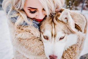 A beautiful blonde hugs her dog