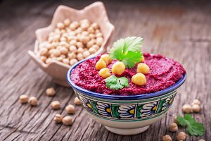 Beetroot hummus with chickpeas and cilantro sprigs in a blue painted bowl on dark wooden background