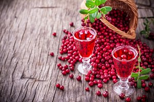 Sweet cranberry liqueur in two glasses on the background of ripe berries