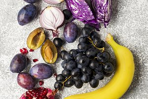 Vegetables and fruits rich in vitamin anthocyanin: bananas, blueberries, red cabbage, sweet purple onions, dark grapes, prunes. Benefits of nutrition for the heart and cardiovascular system. Top view. Copy space