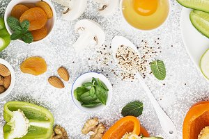 Ingredients for healthy seasonal feeding of green, orange and white flowers: cucumber, zucchini, mushrooms, dried apricots, sweet peppers, oranges, quinoa, almonds, walnut, mint, frisee salad Top view Copy space