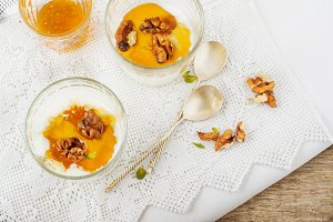 bowl of yogurt with honey and walnuts on a napkin