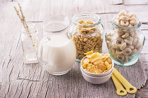 Different types of cereal in glass jars with a jug fresh milk for breakfast