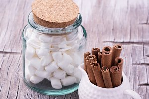 Cinnamon sticks in bucket on wooden background