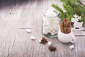 Cinnamon sticks and anise stars on a simple light wooden background